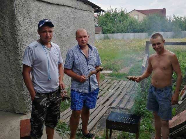 Молодёжь, социально-восстановительного цента для бывших заключённых, жарит шашлык из курицы